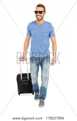 Happy young man with trolley bag on white background