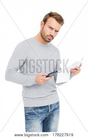 Young man calculating bill on white background