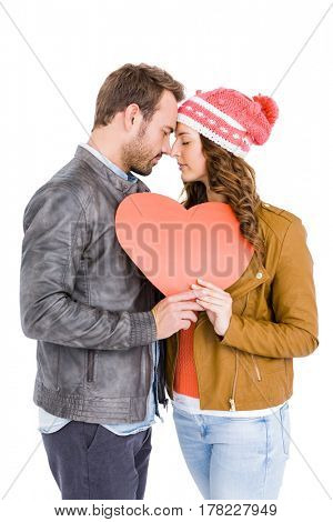 Young couple holding big heart on white background