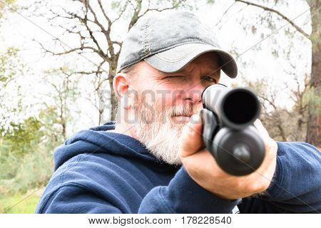 Close up View of Man With White Beard Aiming Shotgun
