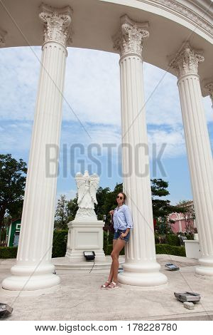 Portrait of a young slender woman leaning against a tall column in a park.