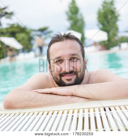 Man with beird on resort pool