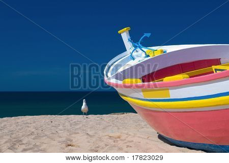 Small brightly painted fishing boat pointing out to sea
