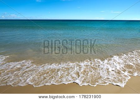 Sandy beach backdrop with calm water and blue sky tropical holiday concept