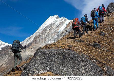 Mountain Climbers Team with Backpacks and walking Poles walking up along rocky Ridge toward high Altitude snowy Peak