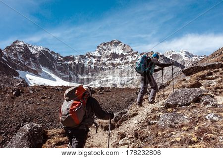 Mountain Climbers Team with Backpacks and walking Poles walking up on rocky Terrain toward high Altitude snowy Peak