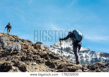 Silhouettes of Mountain Climbers with Backpacks and walking Poles walking up along sharp Ridge toward high Altitude snowy Peak