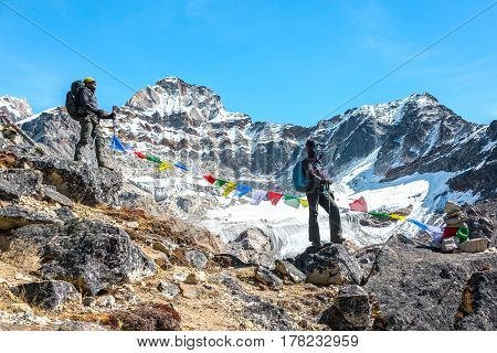 Man and Woman in Alpine Climbers clothing and Gear staying on rocky Ridge and overlooking further route along with traditional colourful Nepalese flags and high Mountains on background.