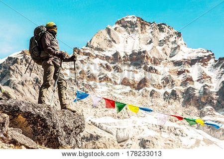 Mature Mountain Climber staying on rocky Ridge in high Altitude Mountains along with traditional colourful Nepalese Flags and snowy Summits and Glacier on Background