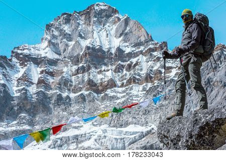 Male Mountain Climber staying on rocky Ridge in high Altitude Mountains along with traditional colourful Nepalese Flags and snowy Summits and Glacier on Background