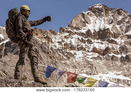 High Altitude Mountain View and Alpine Climber taking Picture on Mobile Telephone staying on rocky Edge along Nepalese Flags