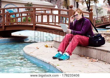 Cute Woman in casual and sporty Clothing sitting in Park next to Pond and using tablet pc device