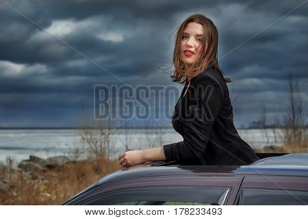 beautiful young girl on the roof of the car