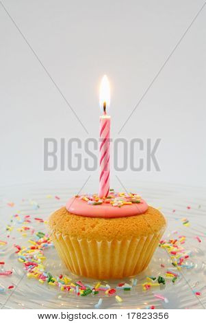 Cupcake with candle on glass plate with candy sprinkles
