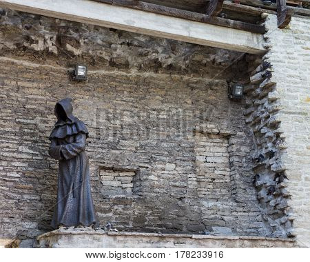 Statue of a monk along the medieval wall in Tallinn, Estonia