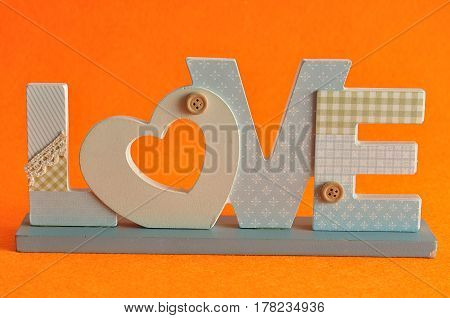 Valentine's Day. Love in blue letters isolated on an orange background