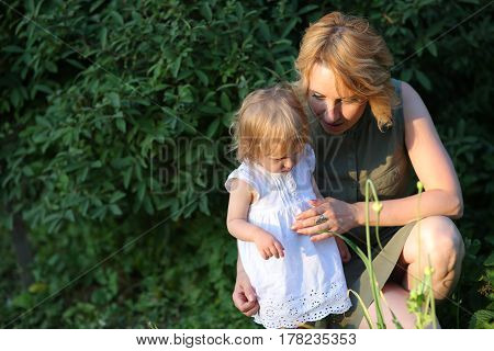woman and daughter eating cucumbers in her garden in the summer