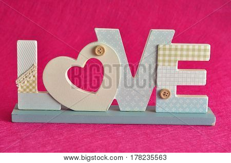 Valentine's Day. Love in blue letters isolated on a pink background