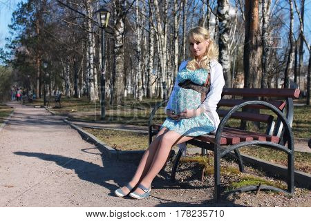 pregnant girl is walking around the city park in early spring