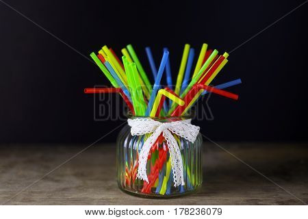 colored plastic cocktail tubes standing in a glass side view
