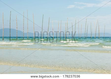 Long bamboo sticks sticking out of sea. Beautiful tropical beach white sand clear blue and green water mountains on background
