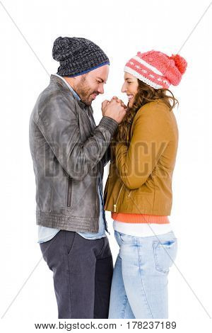 Young couple in warm cloth standing face to face and shivering on white background