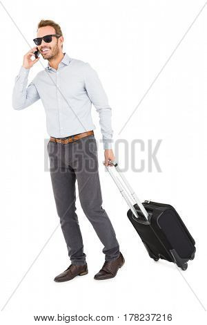Young man holding trolley bag and talking on mobile phone on white background