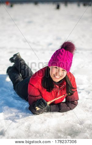 Woman ice-fishing in the winter on the lake
