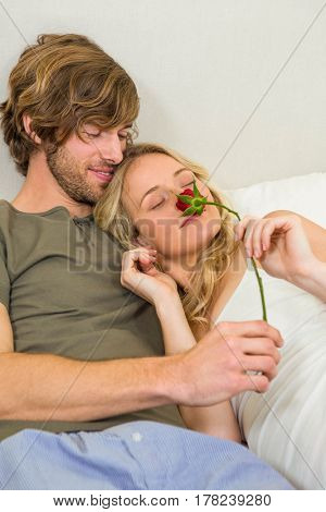 Cute couple cuddling with girlfriend smelling a rose in the bedroom