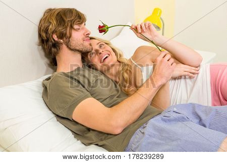 Cute couple cuddling with boyfriend smelling a rose in the bedroom
