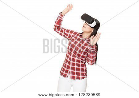 Shocked emotionally woman playing game and watching video in virtual reality and gesturing with rise up. Brunette girl modern in headset of VR surprised looking up with opened mouth.