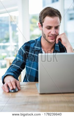 Handsome man working on laptop in a bright office