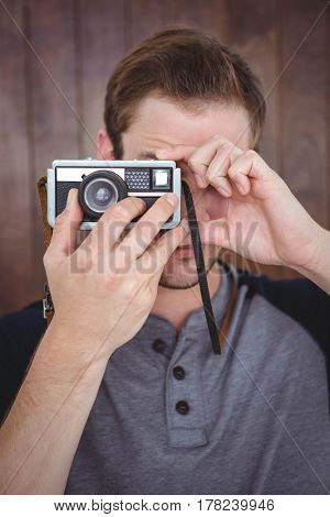 Handsome hipster taking picture with retro camera on a wooden background
