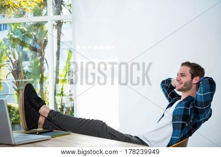 Handsome man relaxing on his desk chair in a bright office