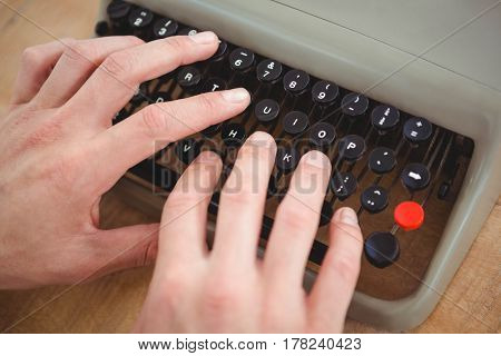 Close up of masculine hands typing on old typewriter on wooden table