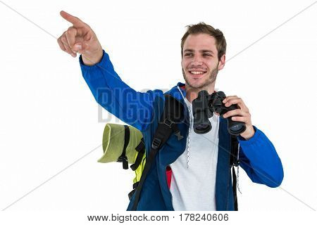 Backpacker hipster pointing while holding binoculars against white background