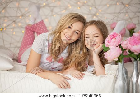 Happy family portrait. Mother and daughter hugging in bed and looking at the camera. Loft interior. Background with lights. Pastel colors. Peony