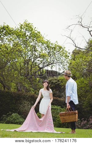 Woman putting picnic blanket in garden and man standing with picnic basket