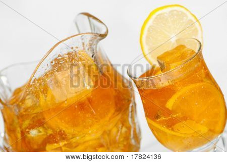Jug and glass of iced tea for the summer - focus on glass