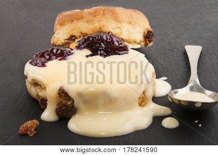 british raisin scone with fresh custard on slate