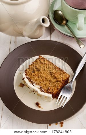 slice carrot cake on a plate with fork cut and teapot