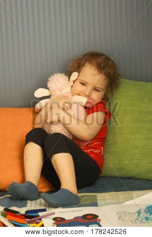 Pretty Little Girl Hugging A Toy Sheep