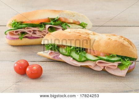 Ham salad baguettes on rustic table with tomato garnish