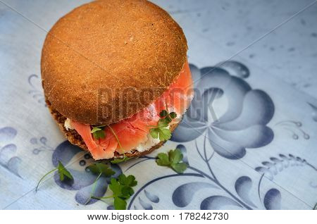 Sandwich with smoked salmon cream cheese parsley on a cork stand