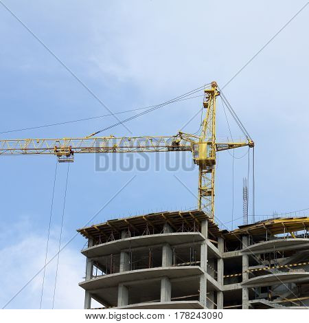 under construction high-rise building with a yellow crane on the background of the sky / next height level