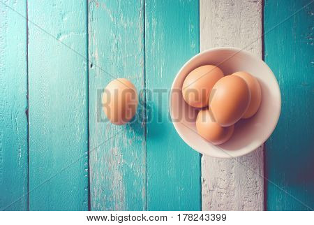eggs in a white bowl on the ocean blue table view from above.