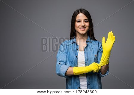 Cleaning lady getting spring cleaning ready putting on rubber gloves. Cleaning woman smiling happy at camera