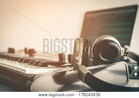 Golden Music Studio headphone lying on working desktop in vitnage tone