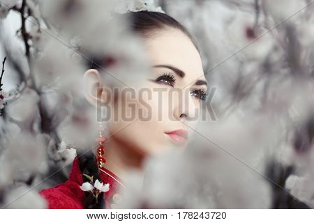 Attractive asian woman wearing kimono standing in blossoming garden.Close-up creative portrait outdoor on the nature. Girl looking away
