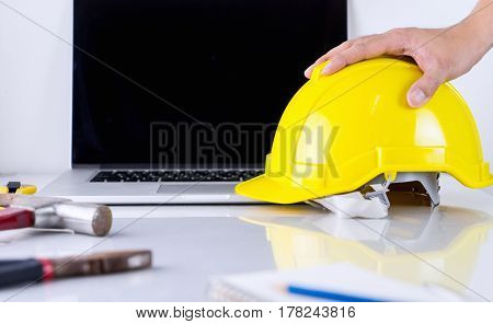 Engineer is picking up safety helmet for outdoor work from office